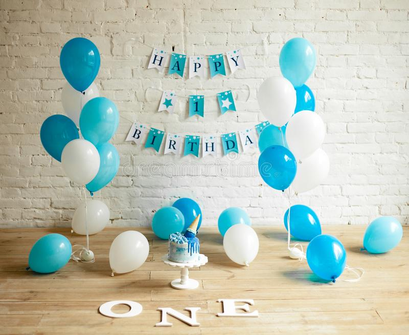 Decorations for one year birthday with balloons, cake and inscriptions on wall and floor. Decorations for one year birthday with a lot of blue and white balloons stock image