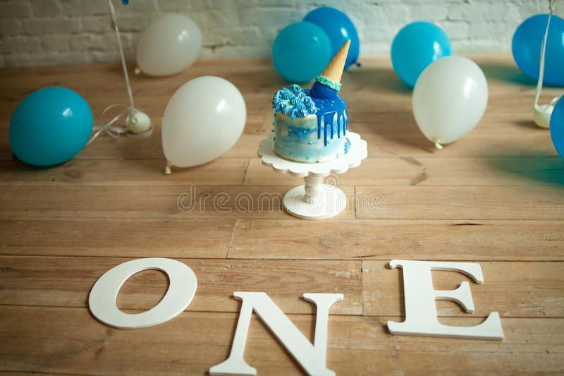 Decorations for one year birthday with balloons, festive cake and inscriptions on floor royalty free stock photography
