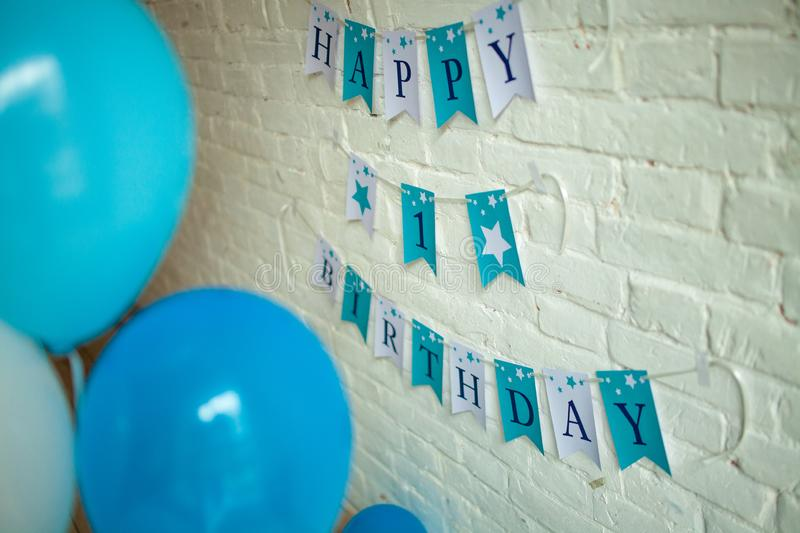 Decorations for one year birthday with blue balloons and inscriptions on wall royalty free stock photos