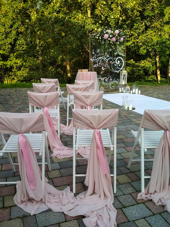 Decorations outdoors for wedding ceremony. Light pink arch with flowers in the park. Vertical photo.  royalty free stock photos