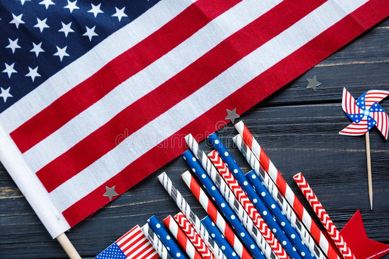 Decorations for 4th of July day of American independence, flag, candles, straws. USA holiday decorations on a wooden background royalty free stock photo
