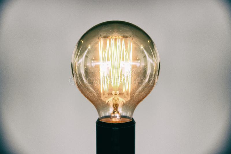 Decorative antique edison style light bulb.Beautiful retro luxury light lamp decor glowing selective focus film grain style effect stock photo