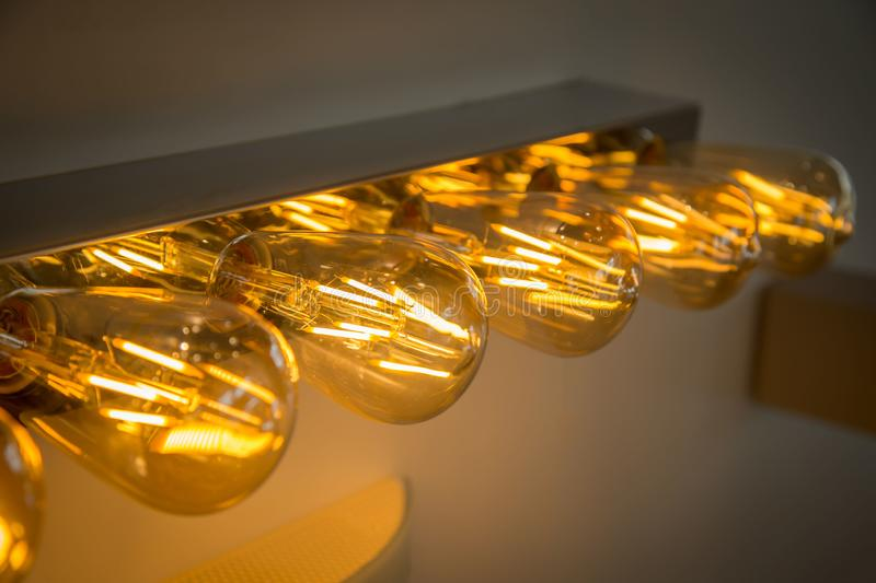 Decorative antique edison style light bulbs against. Industrial pendant lamps against rough wall royalty free stock image