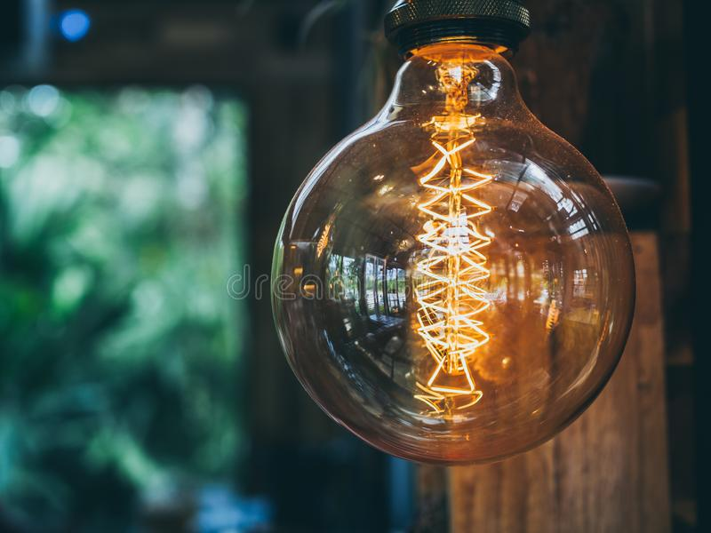 Vintage light bulb in cafe. Decorative antique edison vintage style light bulb on cafe background with copy space royalty free stock image
