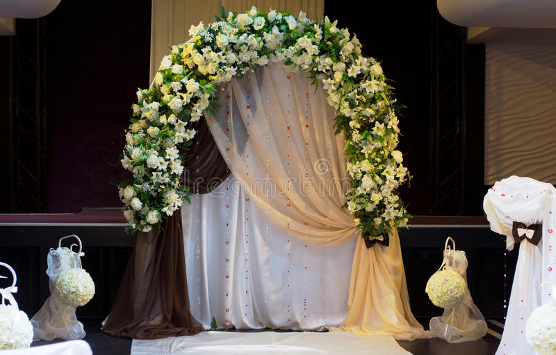 Decorative arched white floral bridal bower. To celebrate a wedding with fun decorations in the foreground at a marriage venue stock images