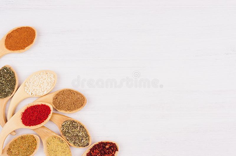 Decorative art border of different spices in bamboo spoons on white wood background, top view, closeup. Decorative art border of different spices in bamboo royalty free stock photos
