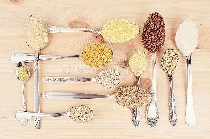 Decorative background of assortment groats grain in silver spoons on wood plank. Healthy food background. Decorative background of assortment groats grain in royalty free stock photo