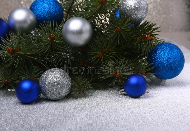 Decorative background with fir branches and red balls on the silver. Christmas card Holiday Concept.  stock images