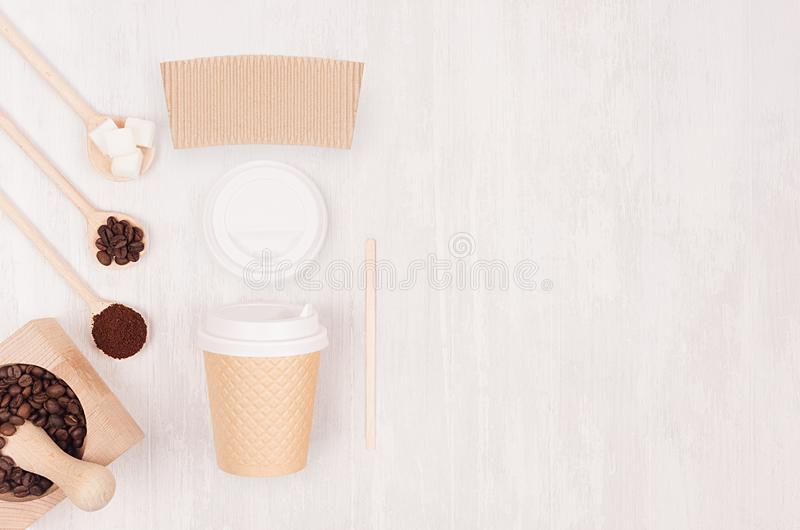 Decorative background for restaurant and coffee shop - blank paper cup, label, mortar with coffee beans, copy space on white wood. Decorative background for royalty free stock photography