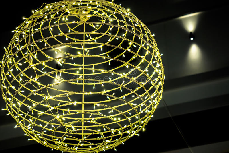 Decorative ball wound with Christmas lights. Decorative skeletal ball wound with lots of yellow Christmas lights, giving multitude point-source illumination stock image