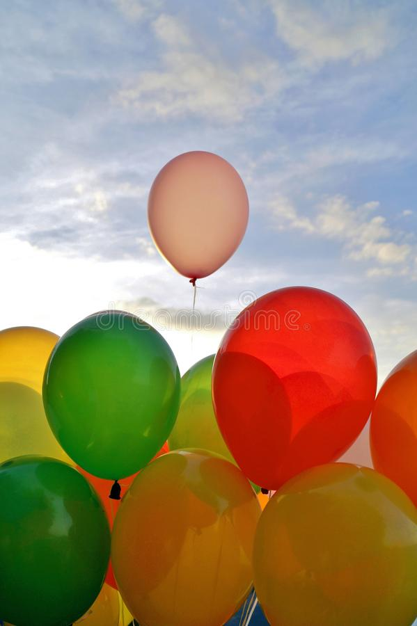 Mix of colorful balloons over blue sky background and sun shining through clouds. royalty free stock photo