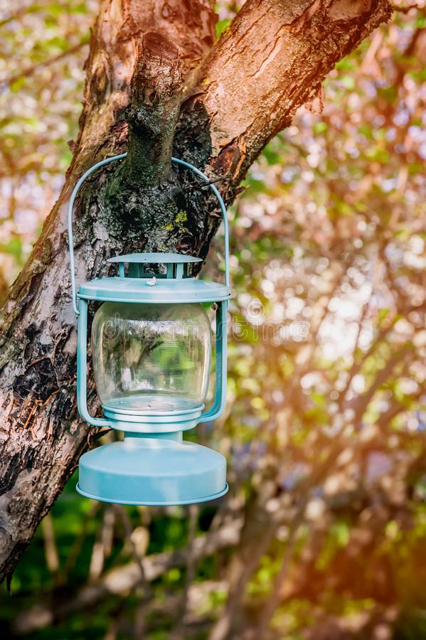 Decorative blue glass Lamp with candles hanging on a tree in the garden.  stock photos