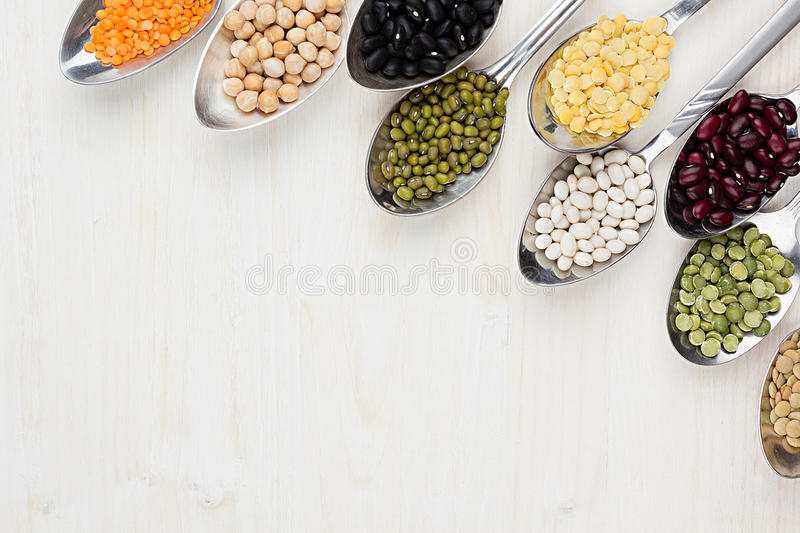 Decorative border of assortment different beans in spoons with copy space on white wood background. Top view, closeup royalty free stock photography