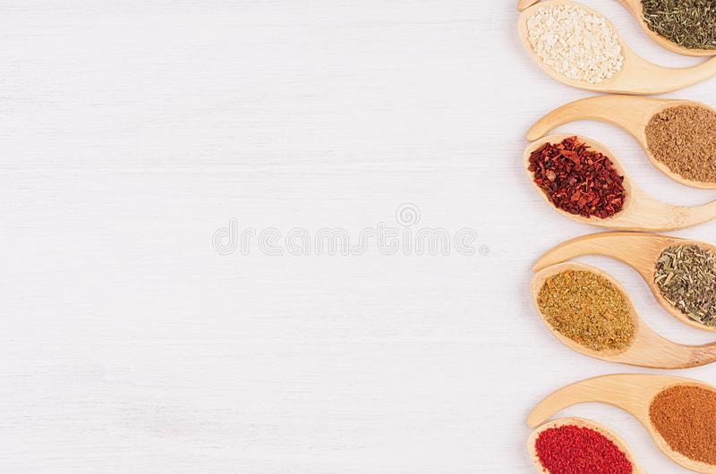 Decorative border of different spices in bamboo spoons on white wood background, top view, closeup, vertical. Decorative border of different spices in bamboo royalty free stock images