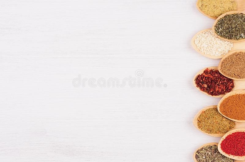 Decorative border of different spices in bamboo spoons on white wood background, top view, closeup, vertical. Decorative border of different spices in bamboo stock image