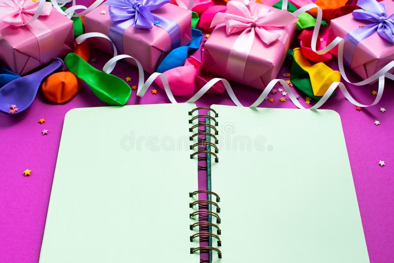 Decorative box composition with gifts satin ribbon bow inflatable balls serpentine purple background A top view of Flat lay stock photos
