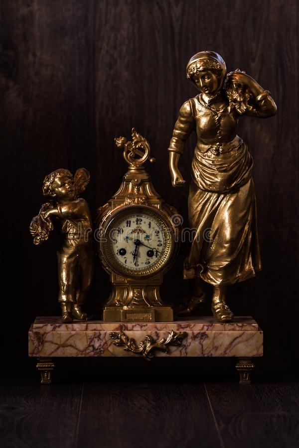 Decorative Brass Clock With Marble Pedestal and Figurines stock photos