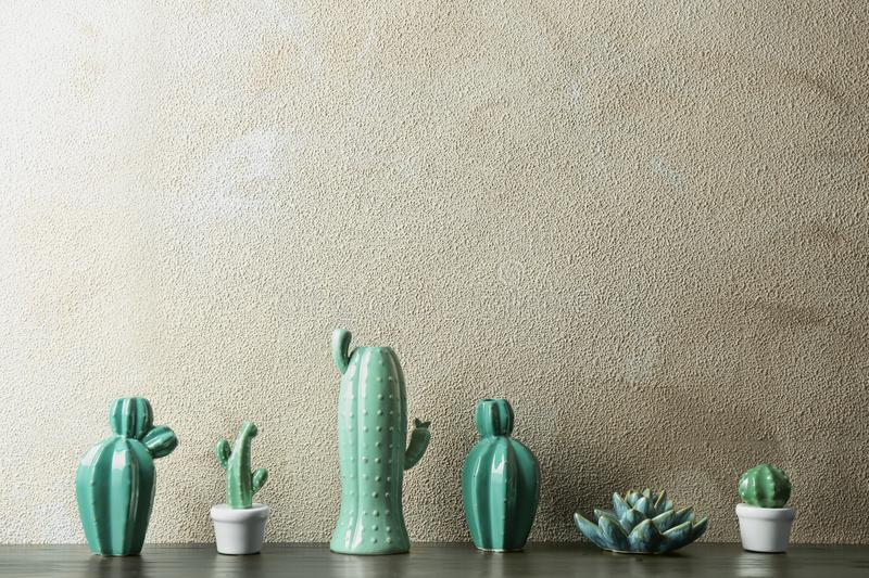 Decorative cacti on table near color wall, space for text. Interior decor stock images