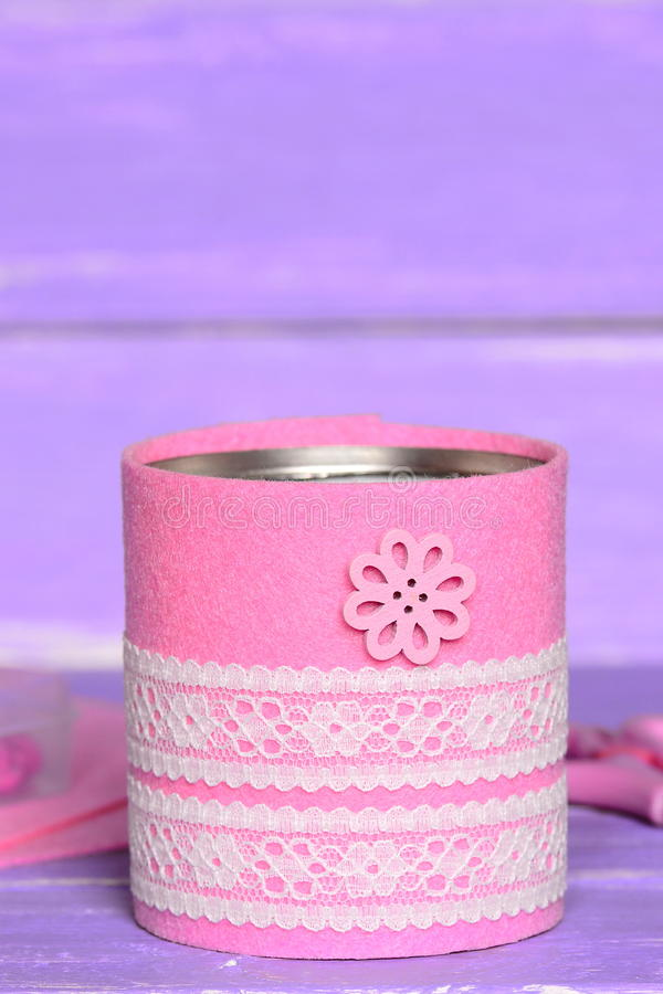 Decorative can on wooden background. Old tin can decorated with pink felt, white lace and flower button. Easy and cheap stock photo