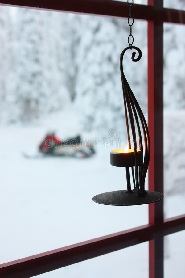 Decorative candle on window and snowmobile stock images