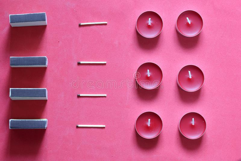 Decorative candles, matchboxes and matches are arranged in a row. On a pink background stock image