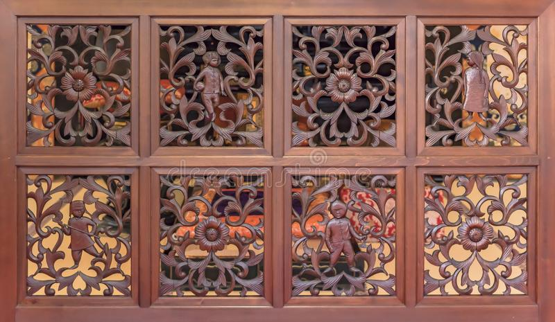 Decorative carvings wood panel with flowers patterns and asian children characters in the choanji temple stock images