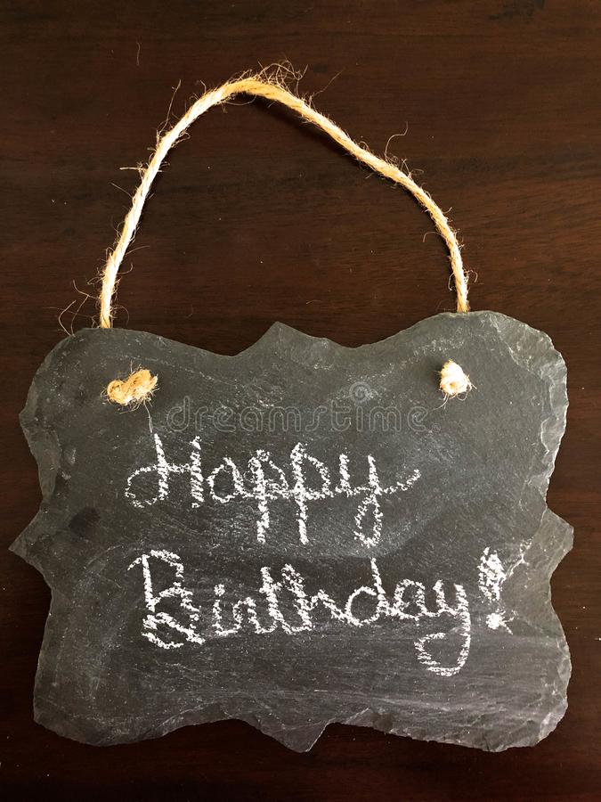 Decorative Chalkboard with Happy Birthday written on wood Background stock image