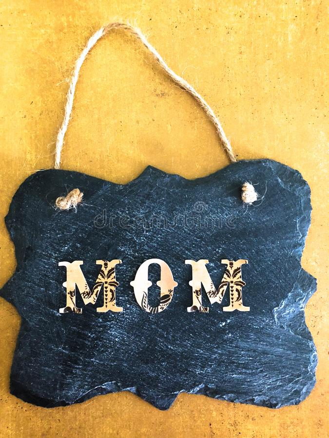 Decorative Chalkboard with MOM written on Yellow and Brown Background stock image
