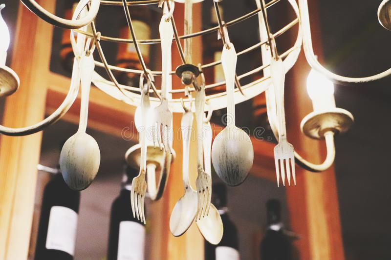 Decorative chandelier made of plastic dishes forks and spoons. Vintage style and the struggle for ecology stock photo