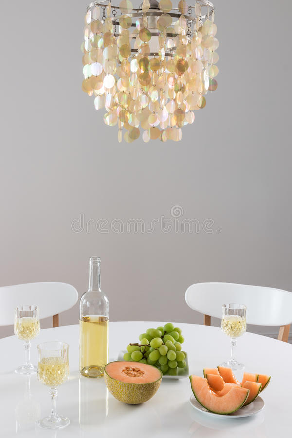 Decorative chandelier and table setting with wine. Decorative chandelier and table setting with white wine and fruits royalty free stock images