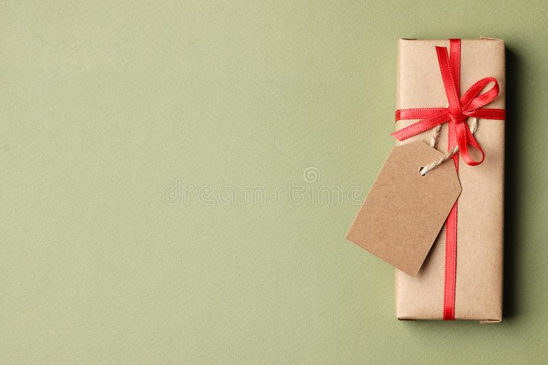 Decorative christmas craft gift box with red ribbon and bow, tag on a green background. Top view. Place for text royalty free stock photos
