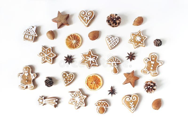 Decorative Christmas food pattern. Winter composition of gingerbread cookies, anise stars, pine cones and dry orange. Fruit slices isolated on white table royalty free stock images