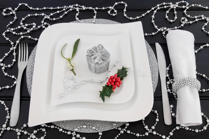 Decorative Christmas Table Setting. Christmas dinner decorative table setting with white porcelain plates, cutlery, linen napkin, holly, mistletoe and silver stock photo