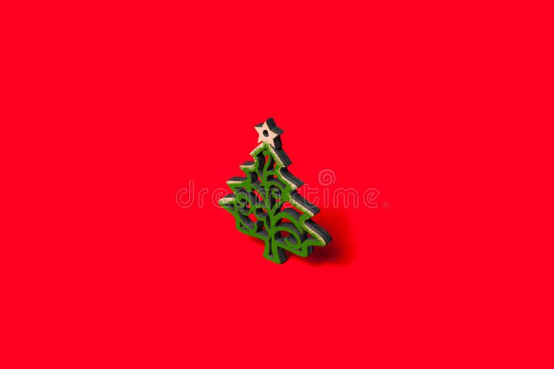 Decorative Christmas tree with green patterns with a star. On top isolated on a red background stock photo