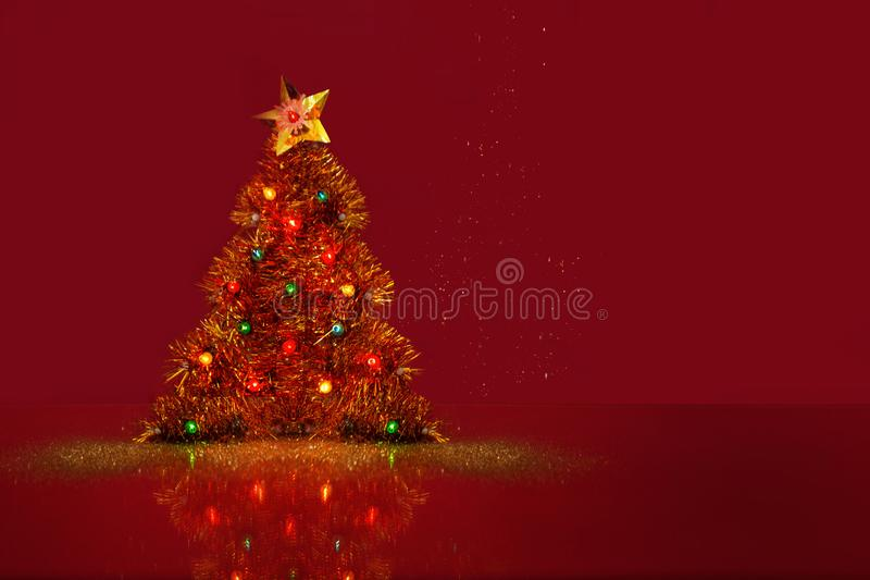 Decorative Christmas tree with a shiny little light bulb. Red background with a space for text. New Year`s Concept stock image