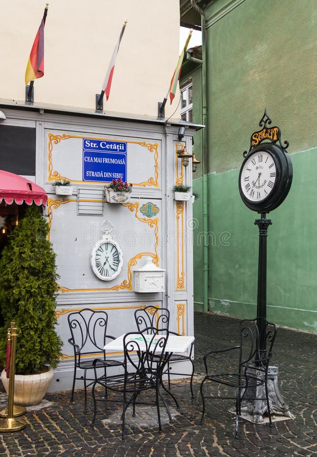 Decorative clock on the leg and table with chairs at the entrance to the cafe on the Cetatii street in a rainy day. Sibiu city in royalty free stock photo