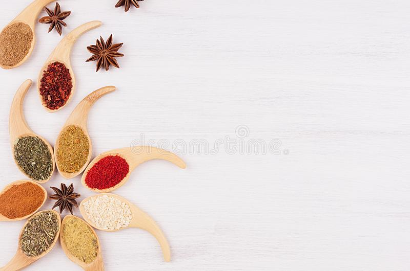 Decorative colorful border of multicolored asian spices and anise star, clove on white wooden background, copy space. Decorative colorful border of multicolored royalty free stock photos