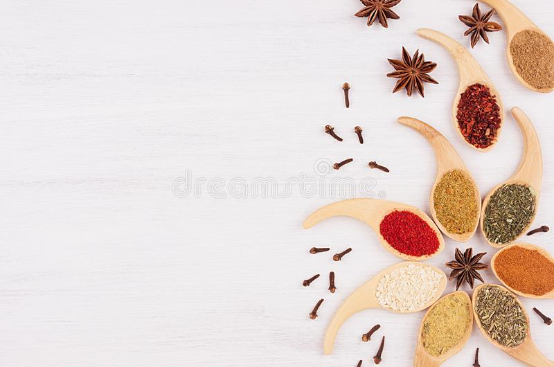 Decorative colorful christmas border of multicolored spices and anise star, clove on white wooden background, copy space. Decorative colorful christmas border royalty free stock photography