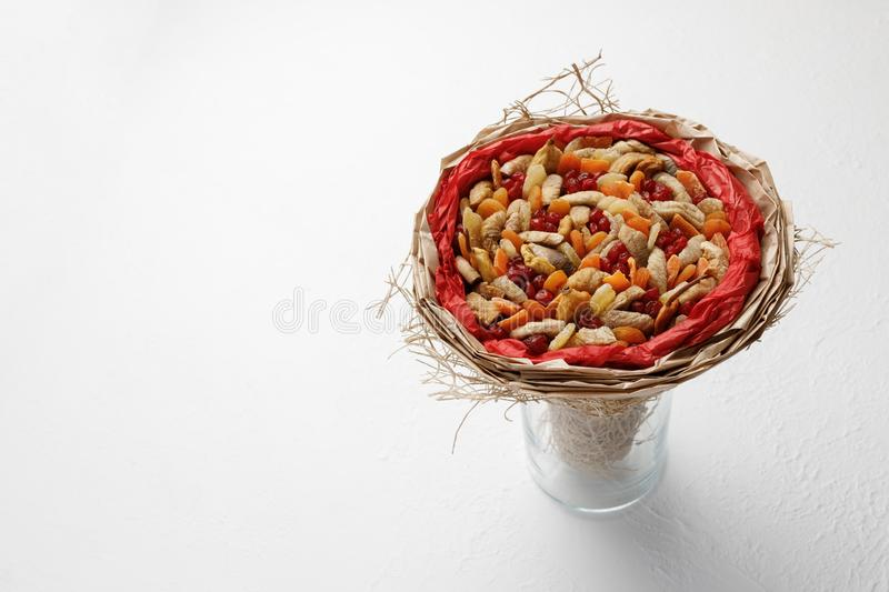 Decorative composition in the form of a bouquet of dried fruits standing in a glass vase on a white table royalty free stock images