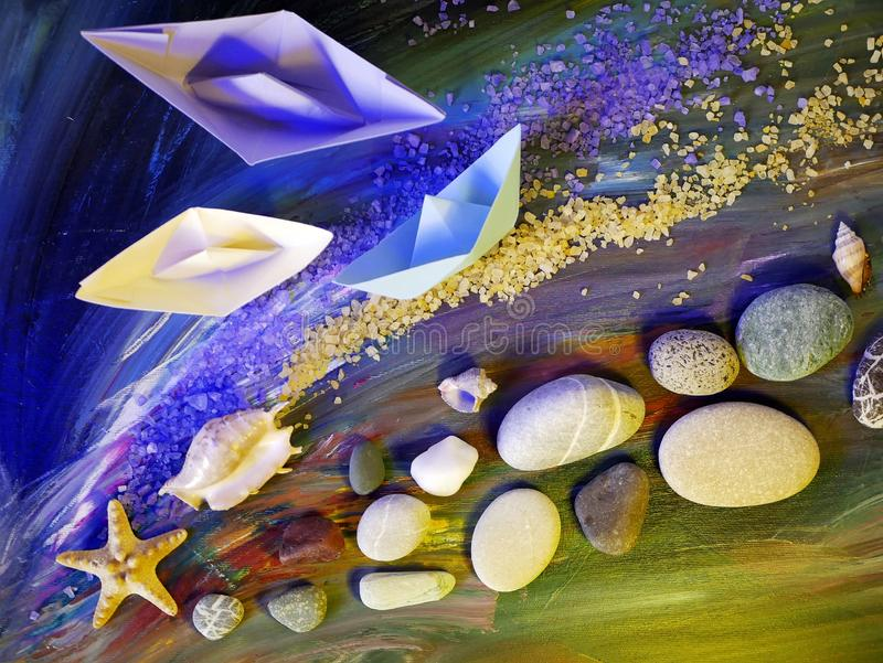 Decorative composition installation - smooth sea stones, sea salt, shells, starfish and paper boats on a blue background stock image