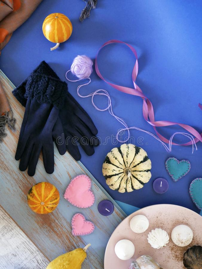 Decorative composition of pumpkins, pears, purple gloves, candles and felt hearts on a blue background royalty free stock image