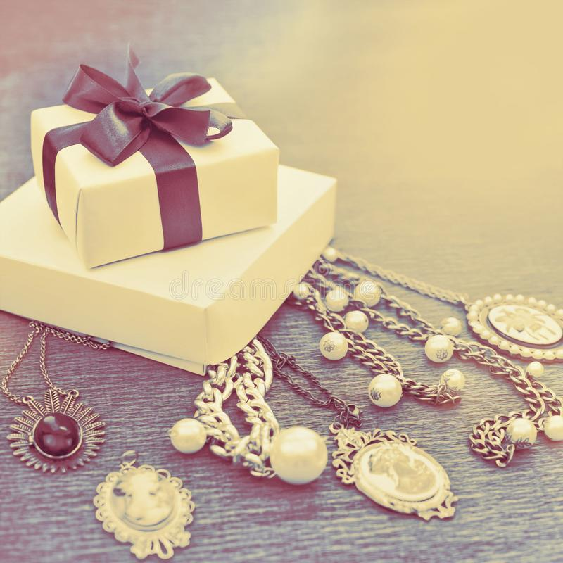 Decorative composition vintage style gift box set decoration ribbon satin bow women`s jewelry necklace comeo pearls wooden backgr. Ound. Retro toning light royalty free stock image