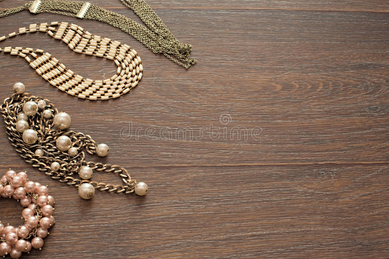 Decorative composition of women`s jewelry on wooden dark background. royalty free stock photo
