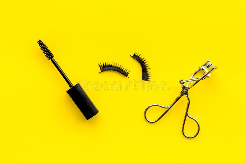 Decorative cosmetic set with lash curler and mascara on yellow woman desk background top view royalty free stock photo