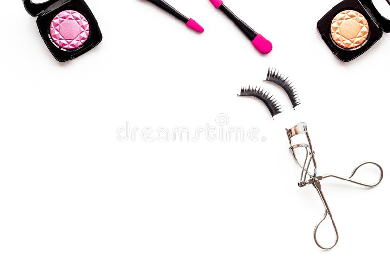 Decorative cosmetic set with lash curler and shadows on white woman desk background top view mock up royalty free stock images
