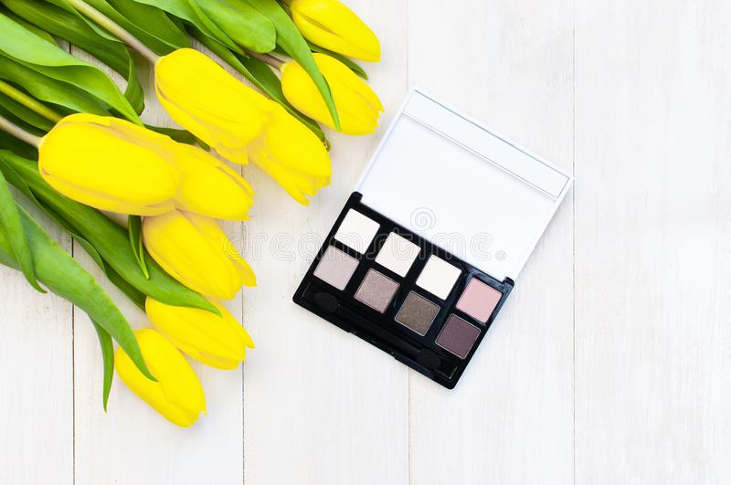 Decorative cosmetics for make-up set of makeup shadows and yellow tulips on a light wooden background top view Flat lay stock photos