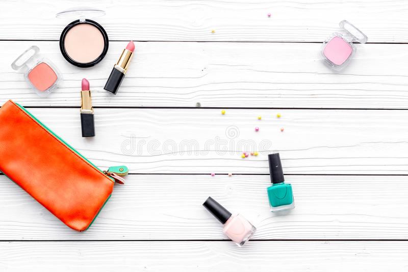 Decorative cosmetics set with beauty bag and nail polish on white desk background top view copy space royalty free stock image