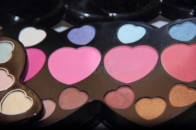 Decorative cosmetics in the shape of a heart: shadows, blush in a large set royalty free stock photos