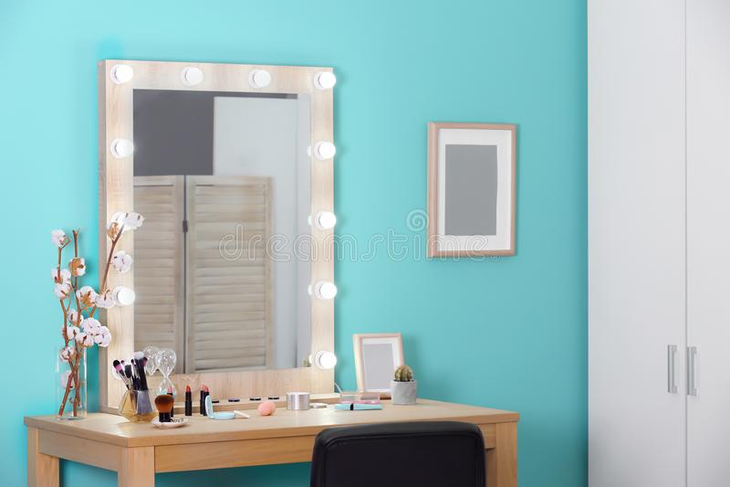 Decorative cosmetics and tools on dressing table. Near mirror in makeup room stock image