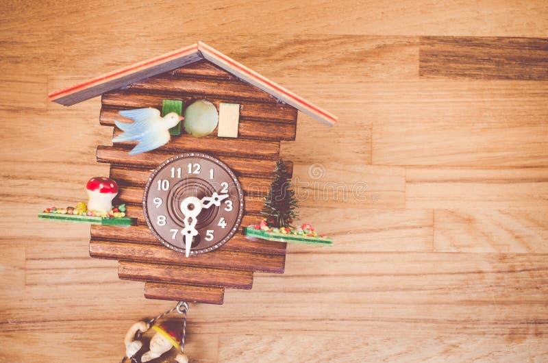 Decorative cuckoo wall clock - analog clock. Ornamental wood house analog cuckoo wall clock dial close up stock photo